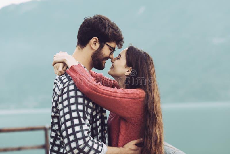 Романтичные пары обнимая outdoors и усмехаясь стоковые фото