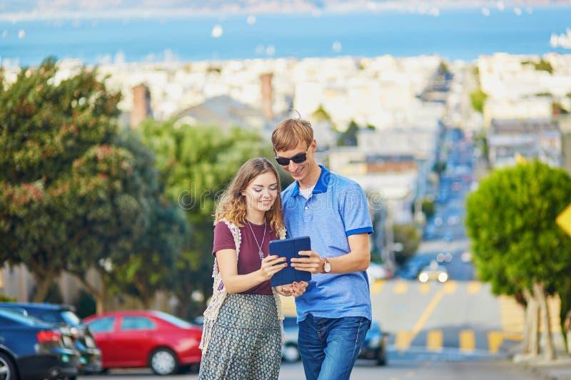 Романтичные пары туристов используя таблетку в Сан-Франциско, Калифорнии, США стоковое фото