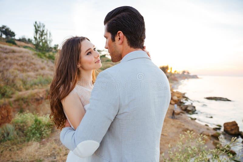 Романтичные пожененные пары стоя на пляже стоковое фото