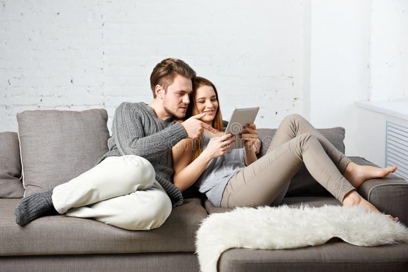 Романтичные расслабленные молодые пары используя планшет на софе стоковая фотография
