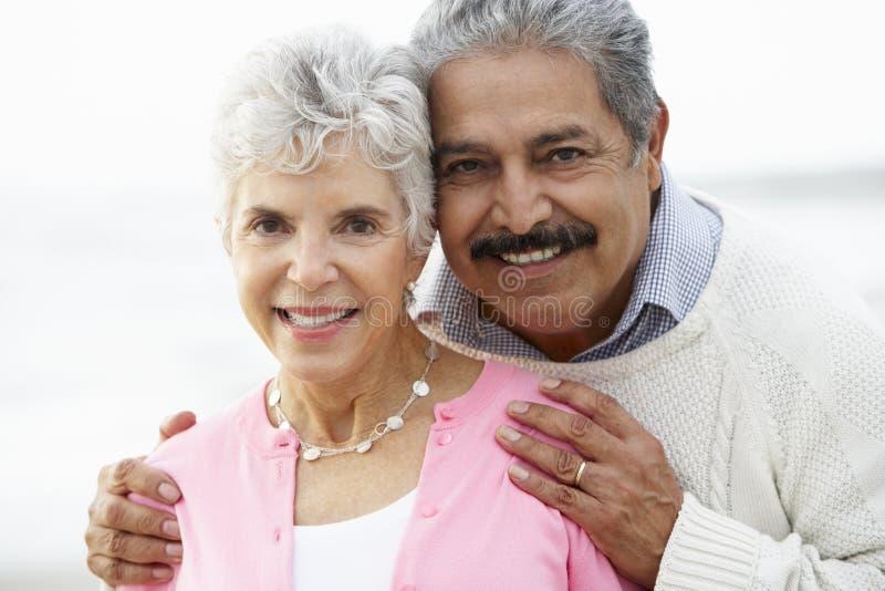 Романтичные старшие пары обнимая на пляже стоковые изображения