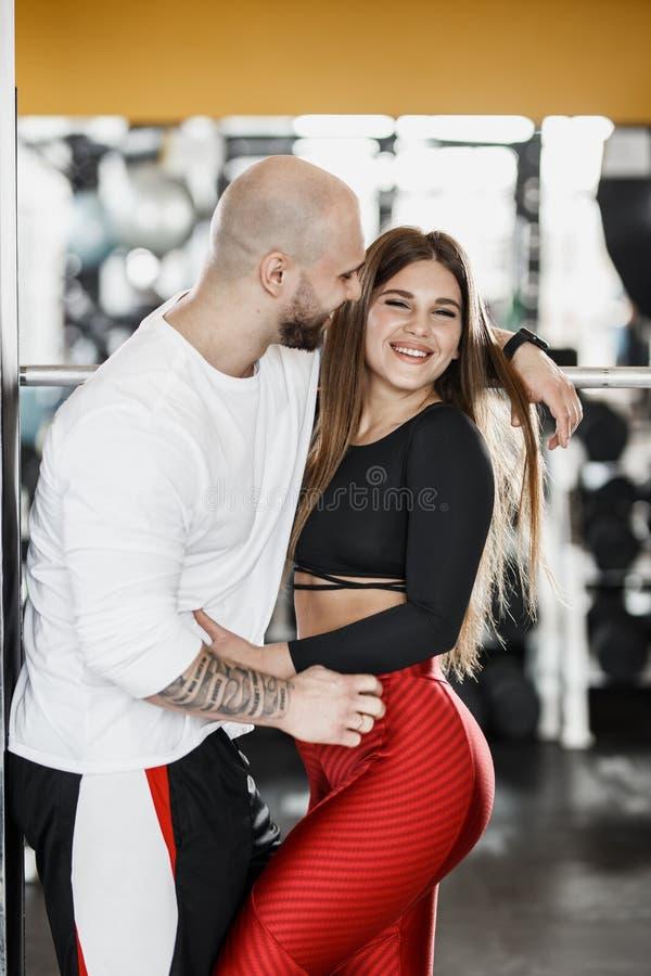 Романтичные счастливые атлетические пары Сильный человек и худенькая красивая девушка обнимают в современном спортзале рядом со с стоковое фото