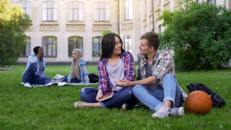Романтичные multiracial пары сидя на лужайке около академии и наслаждаясь одином другого стоковое изображение