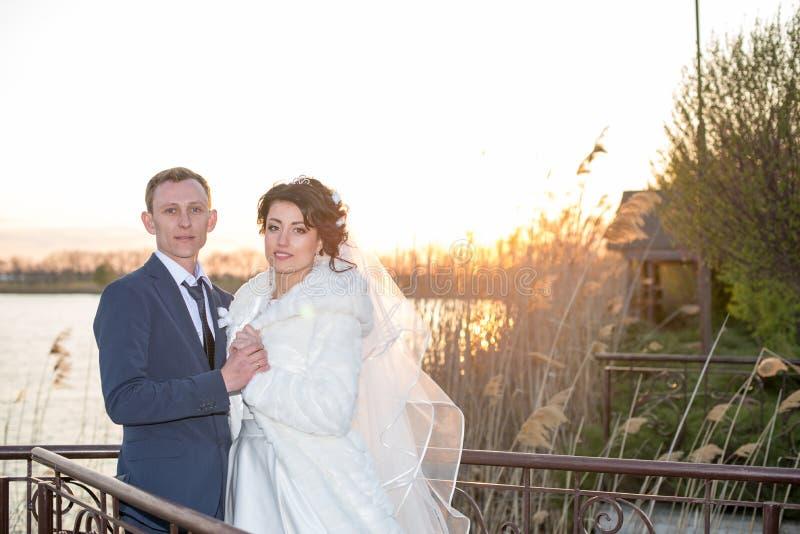 Романтичный ландшафт, пара новобрачных представляя на заходе солнца около реки, жених держит руку невесты стоковые изображения