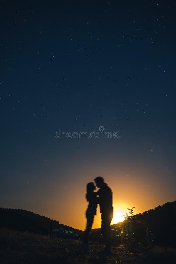 Силуэт молодых пар под звездами Концепция на теме любов романтичный вечер совместно, заход солнца, вертикальное фото стоковые изображения rf
