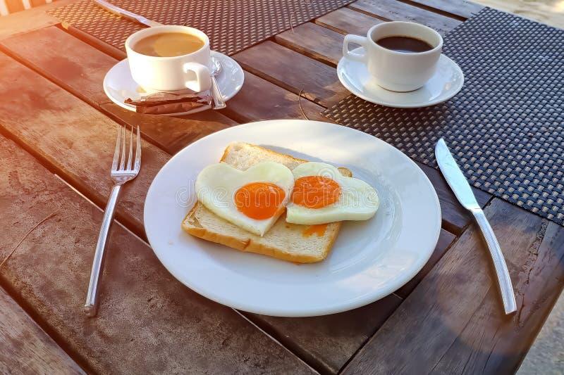 Романтичный завтрак для пар Тост с взбитыми яйцами в форме сердца на белой плите и 2 чашках кофе стоковое фото