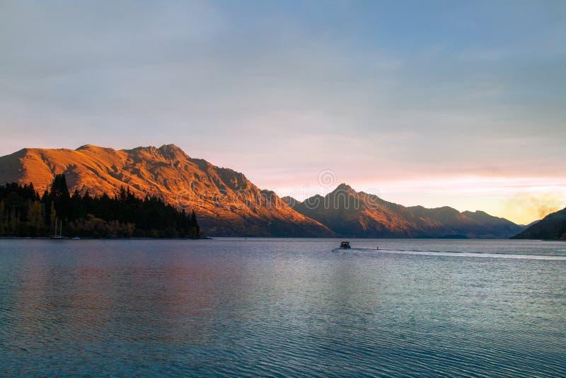 Романтичный заход солнца на озере Wakatipu, золотое отражение солнца на Вальтер и пик Сесиль, Queenstown Новая Зеландия стоковые изображения rf