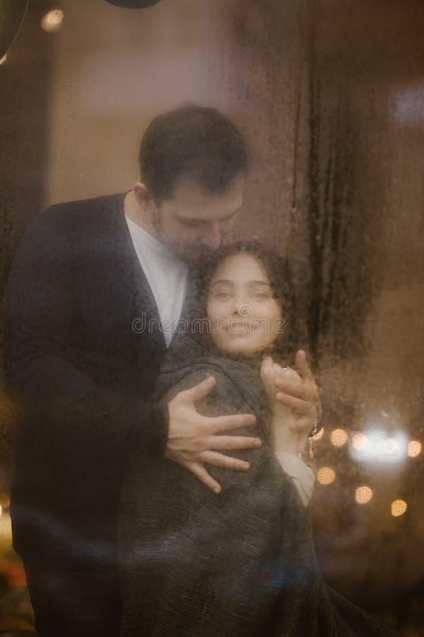 Романтичный любящий парень обнимает его счастливое положение девушки за влажным окном со светами стоковые фотографии rf