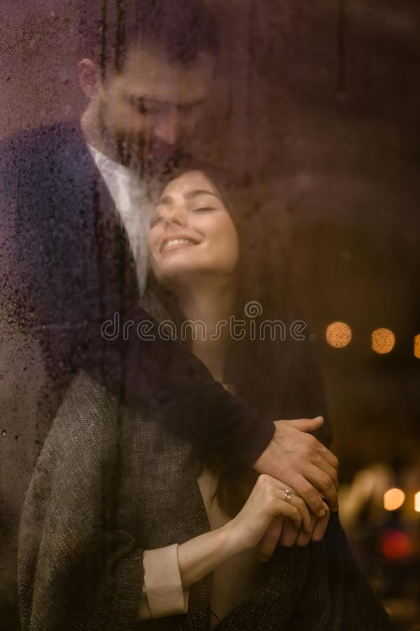 Романтичный любящий парень обнимает его счастливое положение девушки за влажным окном со светами стоковое фото rf