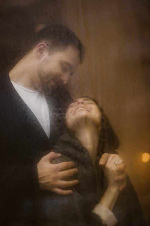Романтичный любящий парень обнимает его счастливое положение девушки за влажным окном со светами стоковые изображения rf