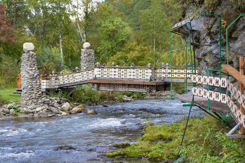 Романтичный мост над потоком в саде стоковое фото