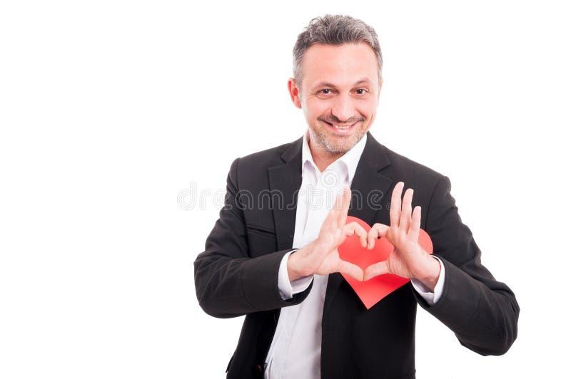 Романтичный молодой человек держа сердце сформировал карточку валентинки стоковая фотография