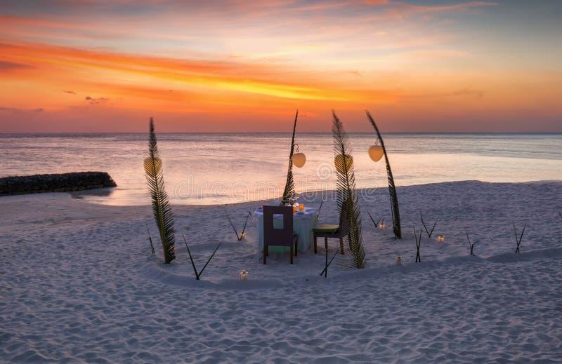 Романтичный обедающий настроенный на тропическом пляже стоковое фото