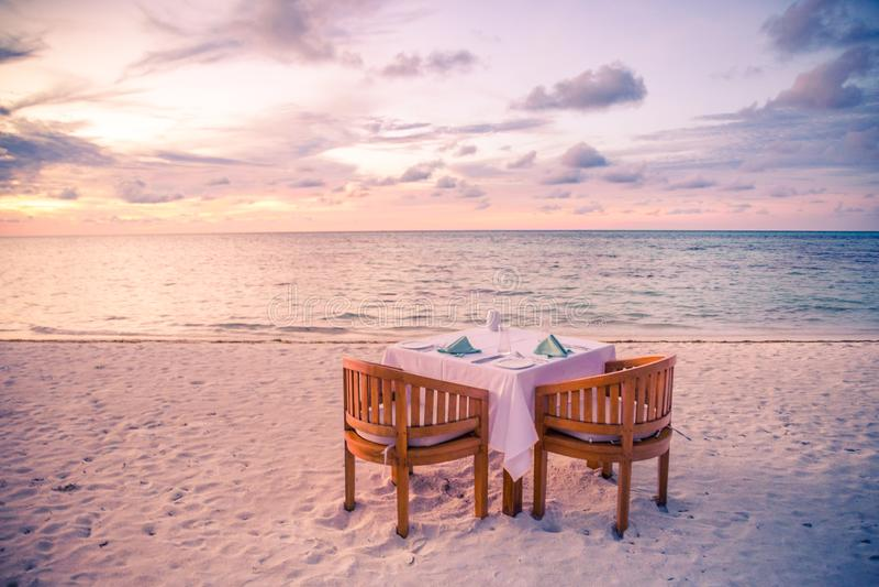 Романтичный обедающий пляжа таблица 2 идилличный заход солнца, тропический курорт или гостиница, пляж захода солнца стоковое изображение