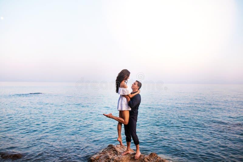 Романтичный ans танцев пар усмехаясь на заходе солнца стоковые фото
