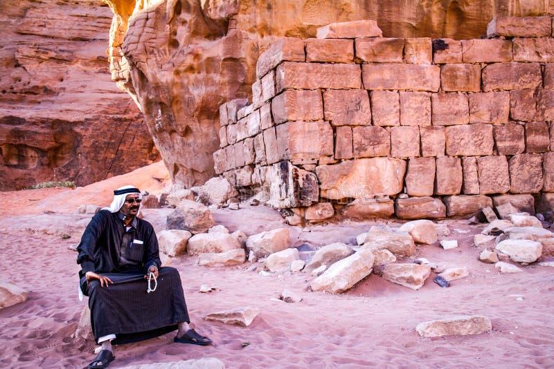 РОМ ВАДЕЙ, ДЖОРДАН - ноябрь 2009: Человек бедуина в традиционной одежде сидит рядом с руинами дома ` s t e Лоренса в роме вадей стоковая фотография