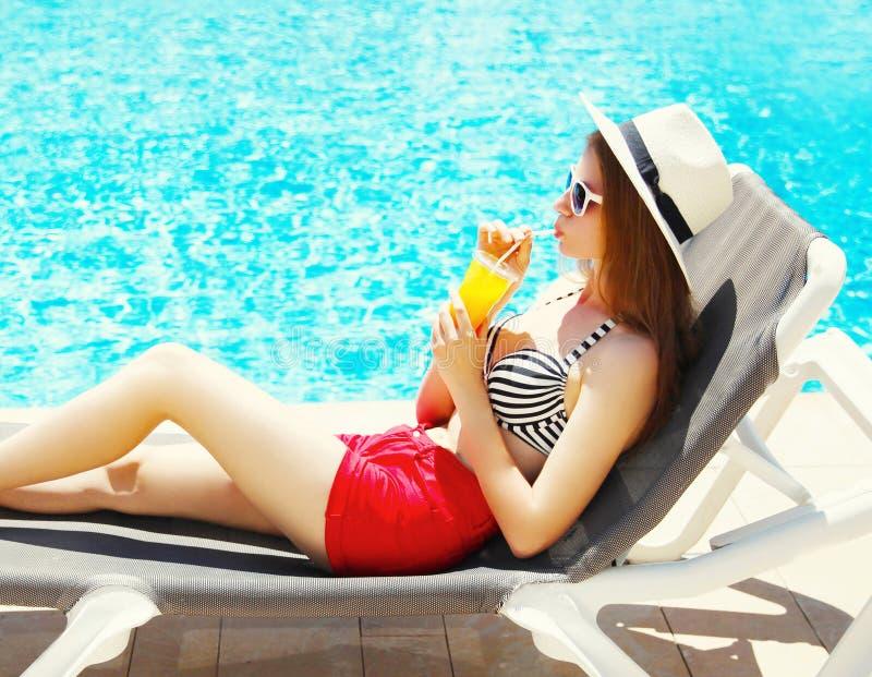 роскошная женщина выпивает сок от чашки на лете на deckchair стоковые фото