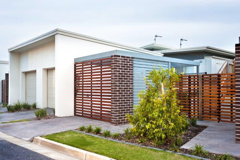 Роскошная лицевая сторона дома с деревянными стробом и садом стоковое изображение