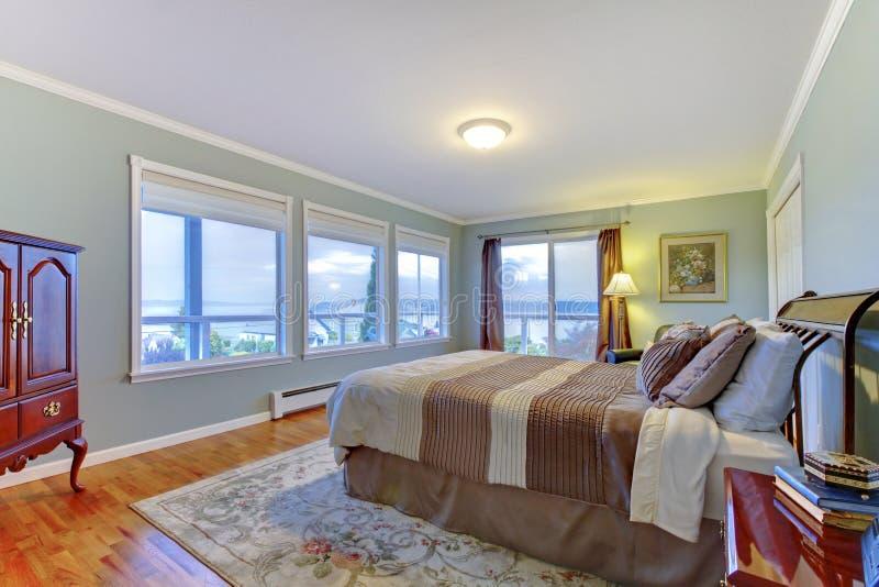 Роскошная домашняя спальня хозяев с голубыми стенами, большой коричневой кроватью и паркетом стоковое фото rf