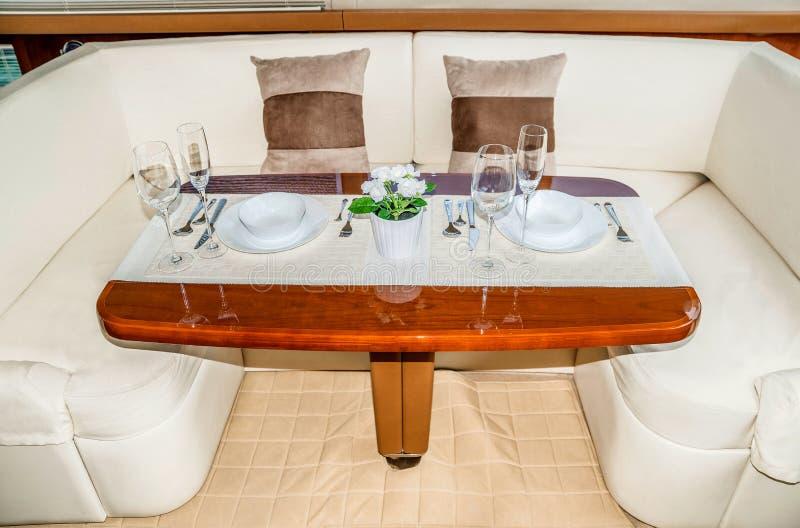 Роскошная сервировка стола обеда на интерьере яхты стоковое изображение rf