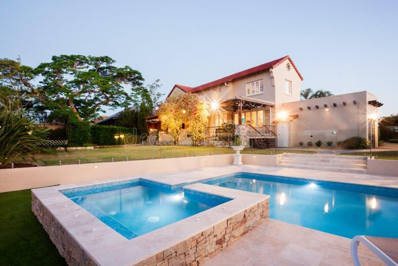 Роскошное украшение сада дома с стороной бассейна стоковое изображение