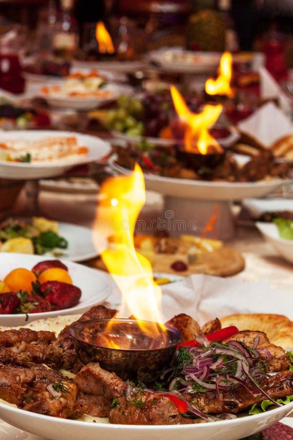 Роскошно украшенная таблица с мясом и огнем жаркого стоковое фото rf