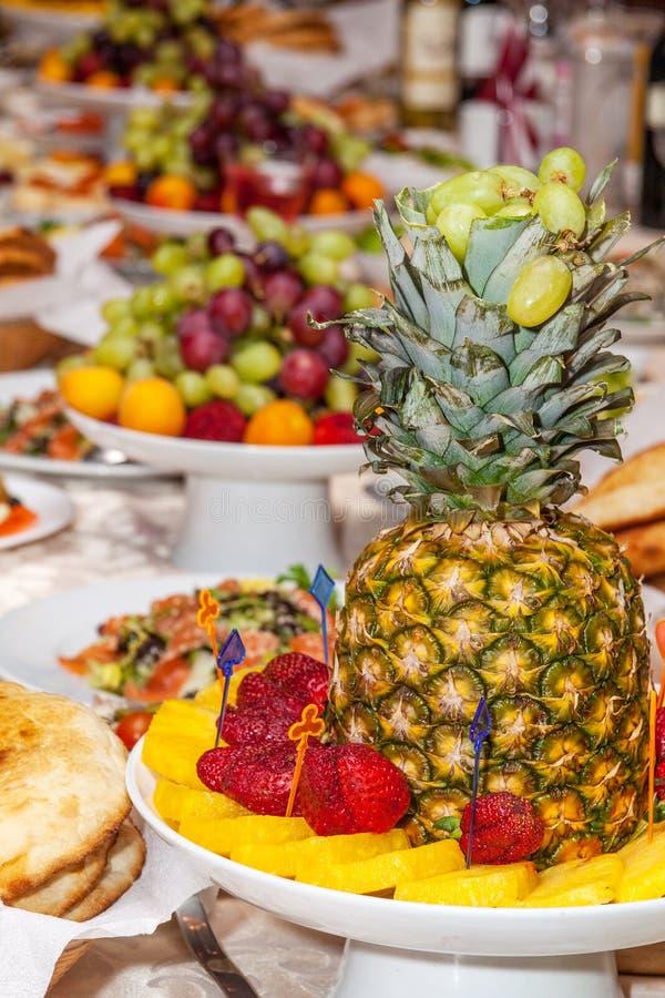Роскошно украшенная таблица с тропическими плодоовощами, клубниками, хлебом и ананасом стоковые фотографии rf