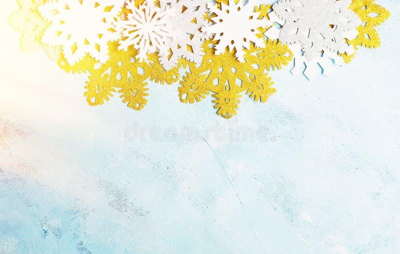 Роскошные белые и золотые снежинки на свете - голубой предпосылке Зима, рождество, концепция Нового Года стоковая фотография