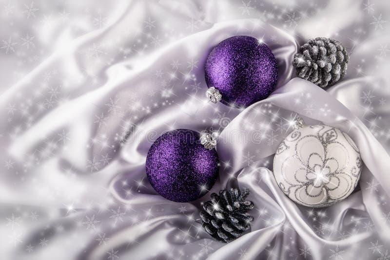 Роскошные конусы серебряной сосны шариков рождества на белом украшении рождества сатинировки совместили фиолетовые и серебряные ц стоковое изображение