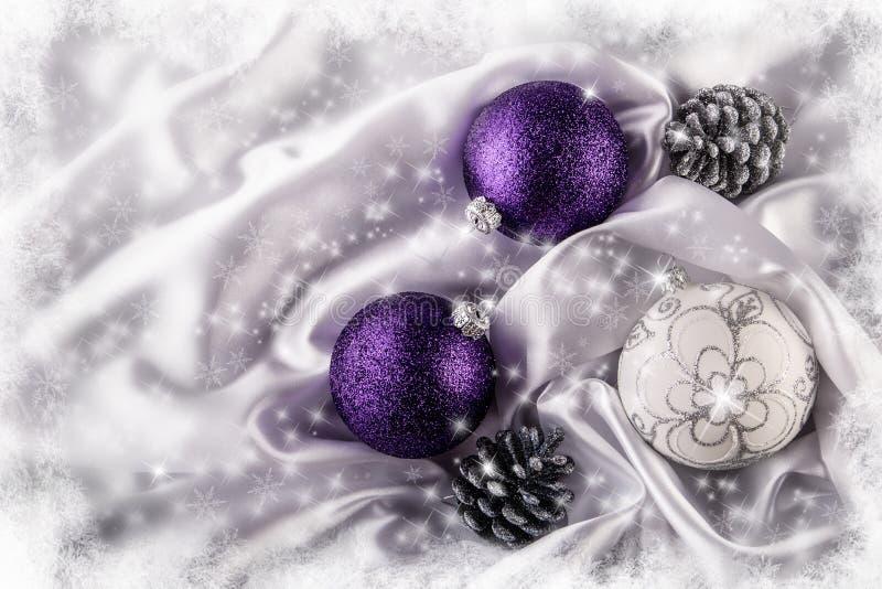 Роскошные конусы серебряной сосны шариков рождества на белом украшении рождества сатинировки совместили фиолетовые и серебряные ц стоковые фото