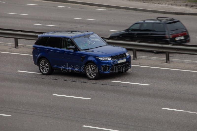 Роскошный автомобиль голубой Range Rover быстро проходя на пустом шоссе стоковое изображение