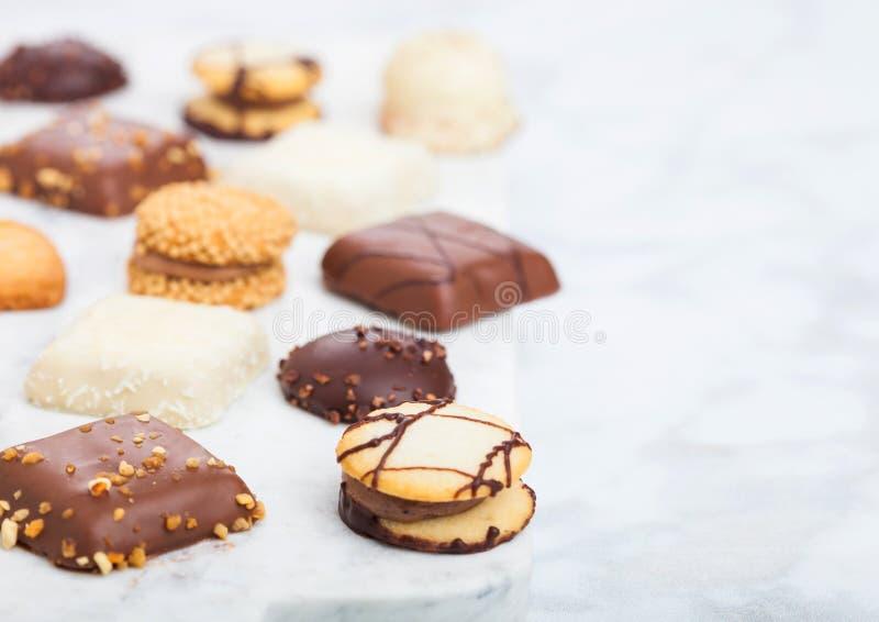 Роскошный бельгийский выбор печений шоколада и печенья на мраморной доске и белой предпосылке кухонного стола стоковые изображения rf