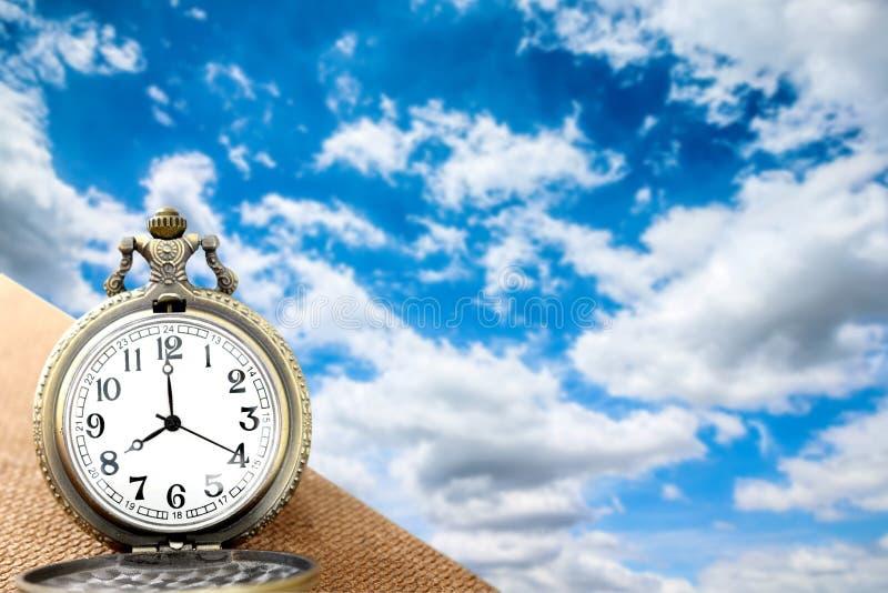 Роскошный винтажный золотой карманный вахта на деревянном над голубым небом с пасмурной предпосылкой, абстрактной для концепции в стоковые фотографии rf