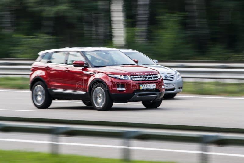 Роскошный красный Range Rover быстро проходя на пустом шоссе стоковое изображение rf