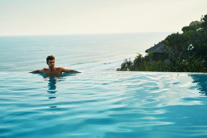 Роскошный курорт Человек ослабляя в бассейне заплыва Каникулы перемещения лета стоковые фотографии rf