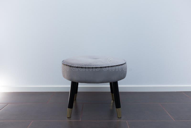 Роскошный небольшой стул перед белыми обоями, на поле известняка со светом стоковые фото