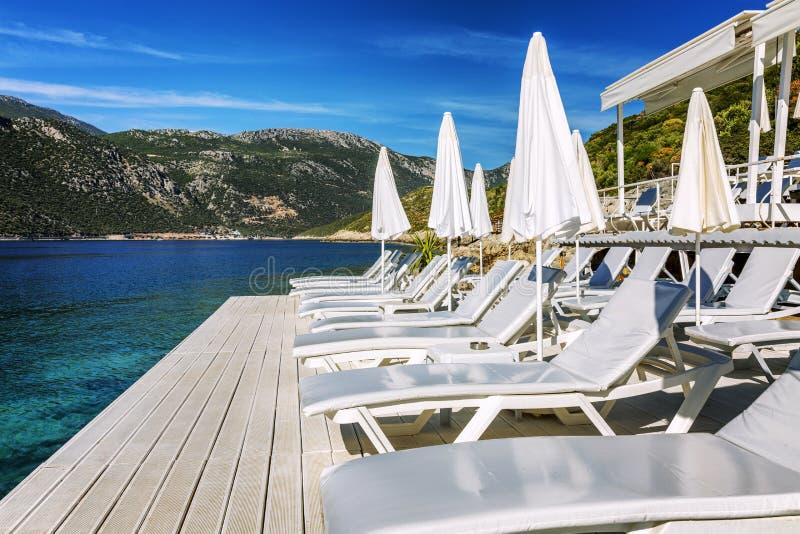 Роскошный пляж с белыми шезлонгами и зонтиками Большее место, который нужно остаться стоковое изображение rf