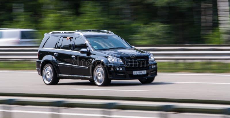 Роскошный черный Benz Мерседес быстро проходя на пустом шоссе стоковое изображение
