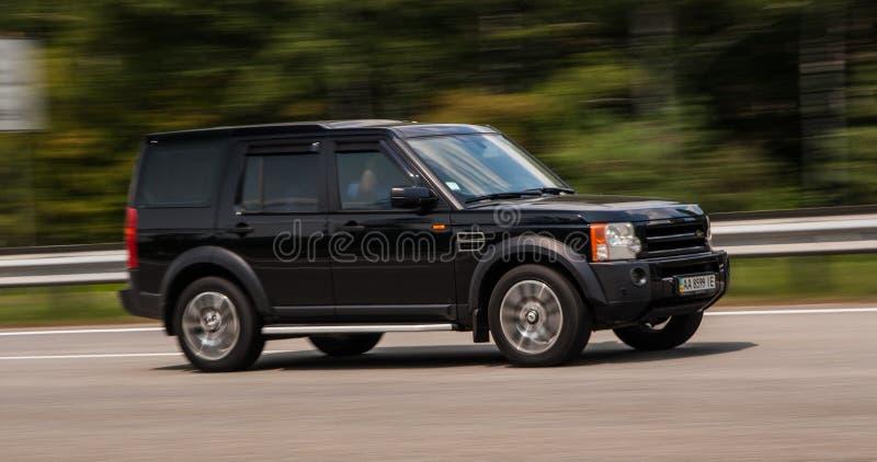 Роскошный черный Range Rover быстро проходя на пустом шоссе стоковая фотография