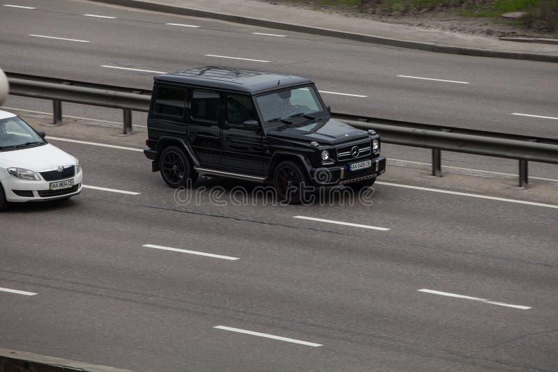 Роскошный Benz g Мерседес черноты автомобиля быстро проходя на пустом шоссе стоковые изображения rf