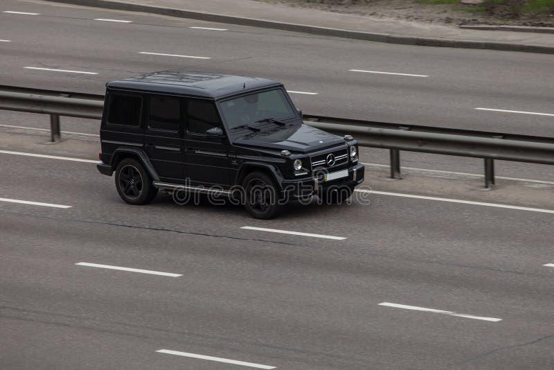 Роскошный Benz g Мерседес черноты автомобиля быстро проходя на пустом шоссе стоковая фотография