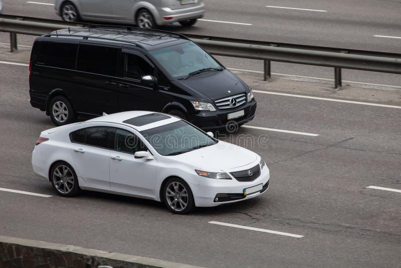 Роскошный Benz Viano Мерседес черноты автомобиля против белого Acura быстро проходя на пустом шоссе стоковое изображение