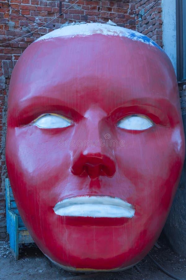 Россия, Казань - 11-ое мая 2019 Красный крупный план маски статуи на предпосылке кирпичной стены grunge стоковые фото