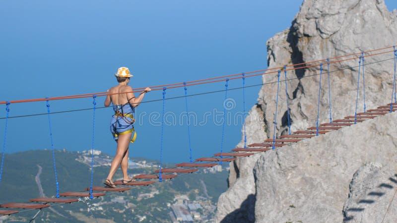Россия, Крым, 3-ье июля 2017 Женщина идя на веревочку на длинном мосте смертной казни через повешение над хлябью стоковые фото