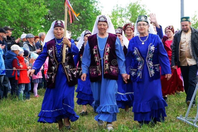 Россия, Магнитогорск, - 15-ое июня 2019 Более старые женщины - участники парада улицы в традиционных костюмах во время Sabantuy - стоковые изображения