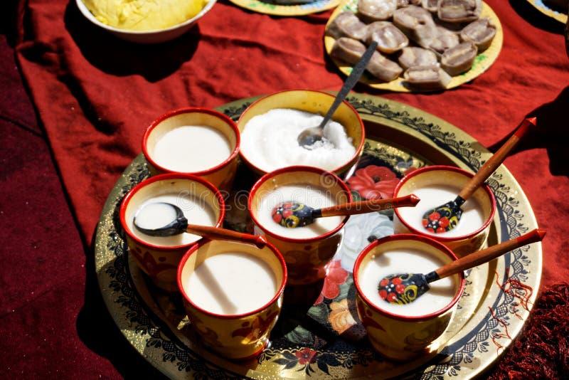 Россия, Магнитогорск, - 15-ое июня 2019 Koumiss - молоко конематки разлил над традиционными национальными деревянными чашками во  стоковое фото