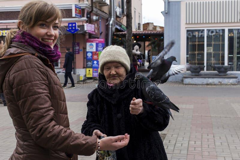 Россия, Москва, может 1, 2018, женщины подавая голуби в улице, редакционной стоковое фото
