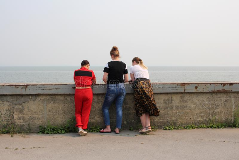 Россия, Новосибирск, 21-ое июля 2019: 3 девушки стоят с их задними частями на портовом районе около остатков запруды гидроэлектри стоковое изображение rf