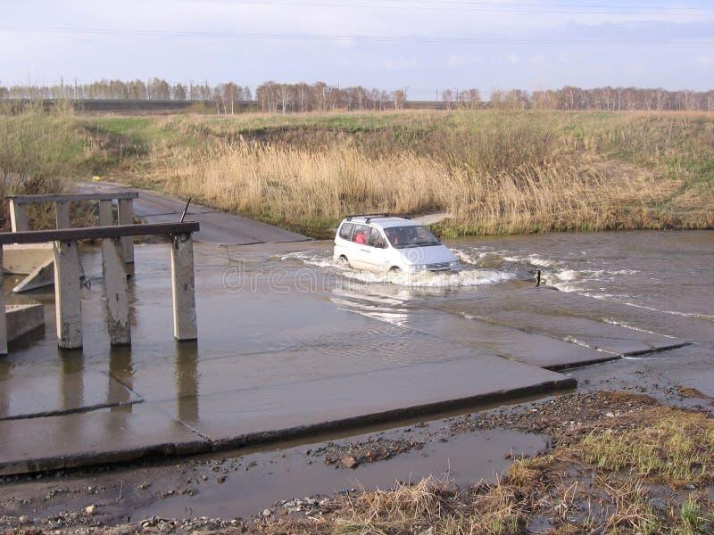 Россия, Новосибирск, 15-ое марта 2013: автомобиль преодолевает затопленный проход дороги опасный через реку в разрушенном потоке  стоковые изображения rf