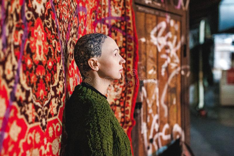 Россия, Новосибирск - 1-ое сентября 2018: лысая женщина с изумляя татуировкой на ее голове портрет на предпосылке красного цвета стоковое изображение